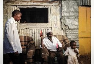 People outside a shack in Kibera. The Kibera slum is the largest slum in Nairobi with around half a million inhabitants.