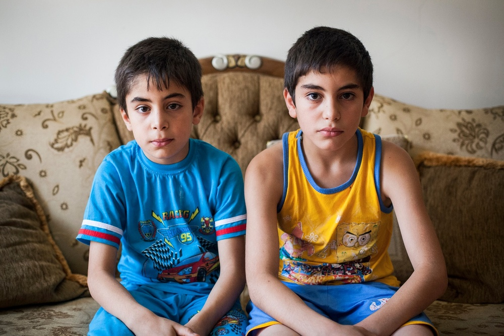 15/08/2014. Erbil, Iraq. Iraqi-Christian  orphan brothers Milad (left) and Wassam (right) sit together in their uncle's house in Ainkawa, where they have been staying for several months.