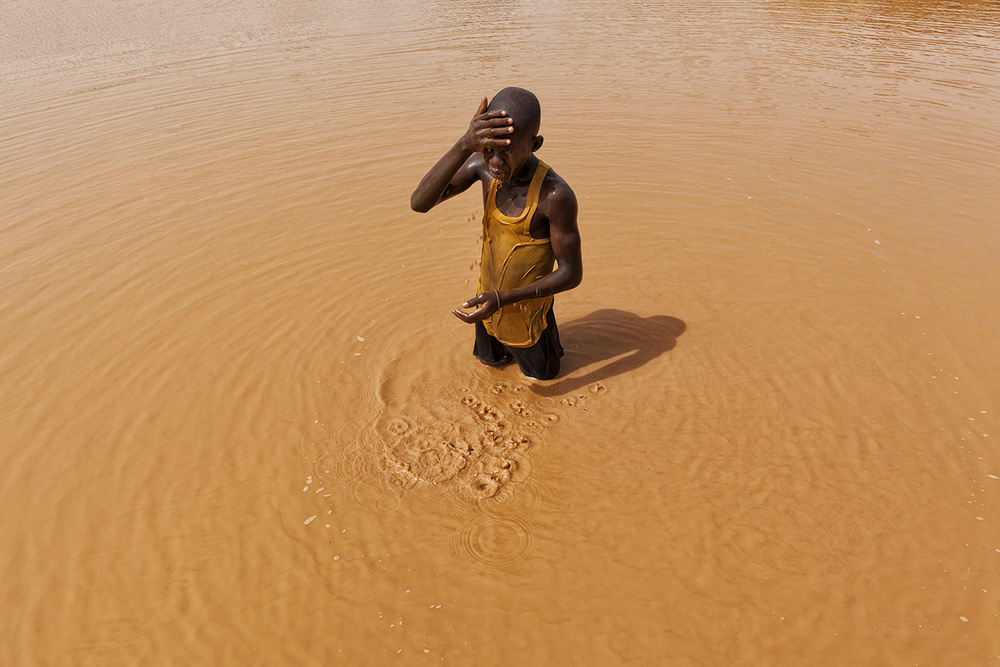 Abdul, 14, is one of hundreds of children working at the Djuga mines. In the rainy season there is water to wash off the dust after a long day. In the dry season, the water is gone.