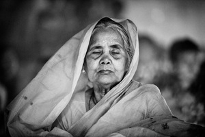 An old Hindu woman sits with lights (Prodip) and prays to God in front of Shri Shri Lokanath Brahmachar Ashram temple during the Rakher Upobash at Barodi, Narayangonj © Suvra Kanti Das, Bangladesh. Shortlist, Arts & Culture, Professional Competition. 2014 Sony World Photography Awards