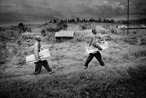 The coffin arrives for the burial of eight-month-old Sakura Lisi, the daughter of a gold miner in Mongbwalu, northeastern Congo. She died from anaemia brought on by malaria. 2004.