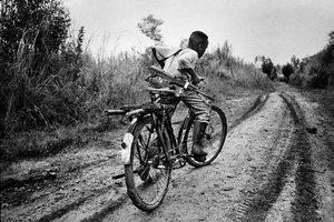 A child soldier rides back to his base in Ituri district, northeastern Congo. 2003.