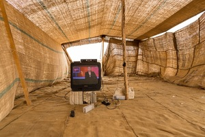 A telly in a make-shift tent. The families in this encampment have settle close to a food packaging plant where many of the adults are working illegally for low pay and the provision of water and electricity. The children, meanwhile, have little to occupy their time. None are in education and the TV offers them a little respite and distraction. © David Brunetti