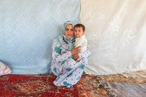 Moonah, her baby and extended family live in an informal camp next to a factory in Mafraq. Abbas, Moonah's husband, and other members (some of them women, some minors) of the camp are working in the factory in exchange for the right to remain on site, water, electricity and a very modest wage. © David Brunetti