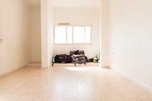 This is the empty flat of a Syrian family with all their belongings in Irbid. The family of five live in this unfurnished room since they arrived in Jordan and share the flat with relatives who also fled the war in Syria. So far they've survived on savings and now that they're finally registered with UNHCR they will receive cash assistance and food vouchers. © David Brunetti