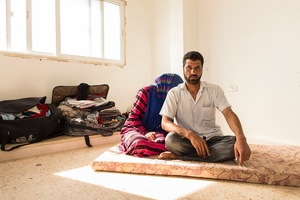 Mohammed and Layan in their new home. Layan was reluctant to have picture taken, she didn't want to show her face but Mohammed said he wasn't afraid and wanted the world to see how he now lives. They are struggling and behind on the rent. They don't know how much longer they will be allowed to stay. Their flat is small and all they possess in the world fits into the suitcases. © David Brunetti