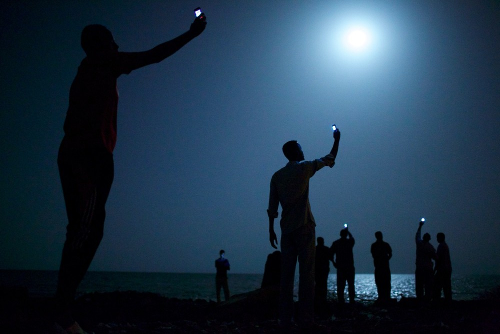 World Press Photo of the Year 2013.  African migrants on the shore of Djibouti city at night, raising their phones in an attempt to capture an inexpensive signal from neighboring Somalia—a tenuous link to relatives abroad. Djibouti is a common stop-off point for migrants in transit seeking a better life in Europe and the Middle East © John Stanmeyer, USA, VII for National Geographic