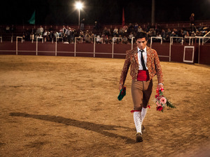 Dinis Caeiro, a member of the Forcados of Évora, leaves the arena after a successful face catch. When the pega is done at the first attempt and with style, the forcado goes around the arena to receive applauses and flowers from the public. © Eduardo Leal