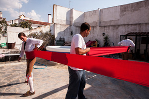 Forcados gets help to put a 5 meters red waistband before the bullfight. The waistband helps to protect their internal organs from the attack of the bull. © Eduardo Leal