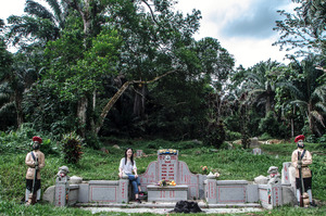 """Cecilia Chong vising her great grandfather's grave,"""" This cemetery brings our family together,what happens?When this is destroyed to build new roads and flats to house the new population?""""© Amrita Chandradas"""