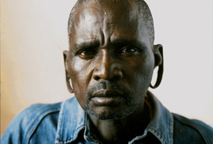 I came here when I was just a boy. That was what you did. You left home and came to the city to look for work. I lived alone in this hostel. Alone with 400 other men. It was dangerous in those days. The football field outside was often covered with blood. — Mr. Mkhize has lived in Madala hostel, in the heart of Johannesburg's affluent suburbs for 15 years. © Adam Broomberg and Oliver Chanarin