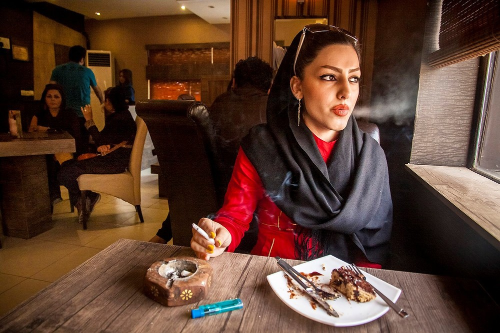 "Sheida, 18, smoking a cigarette in a café. She says "" I feel safe in the café"".  Smoking cigarettes is not restricted by law in Iran, however the girls are afraid of smoking in public places. Traditional men will harass them for doing it. From the series ""Iranian People, Ordinary or Criminals?"" © Mehran Hamrahi"