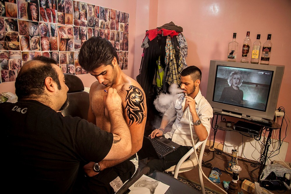 "Mohammad, 27, getting a tattoo. Having a tattoo is considered abominable in Iran, yet some youths get one anyways. People caught with tattoos on their body can be punished, denied employment, or barred from receiving a driver's license. From the series ""Iranian People, Ordinary or Criminals?"" © Mehran Hamrahi"