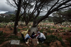 Members of the Oka Boys and Garo Boys visit Mansoer Odendaal's grave site in Observatory for his 18th birthday. Ryan, (red jacket) who was also stabbed, was with Mansoer the night he was killed on the bus. © Charlie Shoemaker